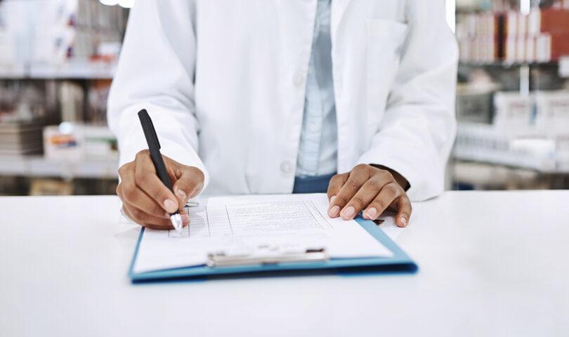 Pharmacist writing on a clipboard