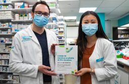 Pharmacists holding vaccine available sign